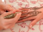 Applying henna design for a natural henna tattoo using a henna cone